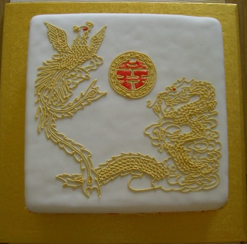 Square, single tier, rich fruit wedding cake with intricate piped golden dragon and phoenix.